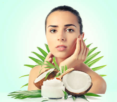 Photo for Coconut oil for skin. Young woman and cosmetic on color background - Royalty Free Image