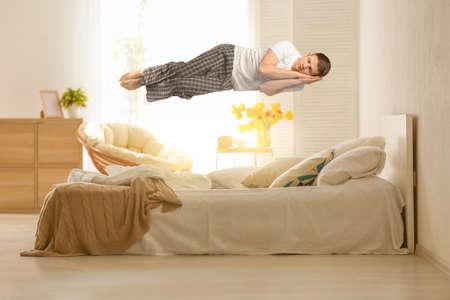 Foto de Sleep paralysis concept. Young man levitating over bed - Imagen libre de derechos