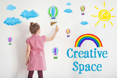 Photo for Art concept. Cute little girl drawing on white wall with space for design - Royalty Free Image