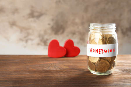 Photo pour Money savings for honeymoon in glass jar on blurred background - image libre de droit