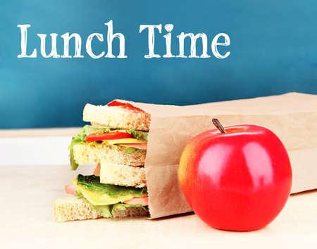 Foto de Lunch time concept. Tasty sandwiches in paper bag and apple on wooden table at classroom - Imagen libre de derechos