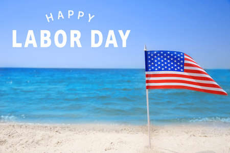 Foto de American flag on beach. Text HAPPY LABOUR DAY on background - Imagen libre de derechos
