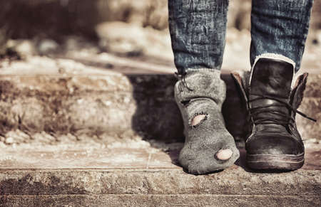 Photo pour Poverty concept. Poor woman wearing tatter sock and one boot - image libre de droit