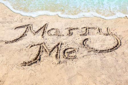 Photo pour Text MARRY ME written on sand near water. Romantic concept  - image libre de droit