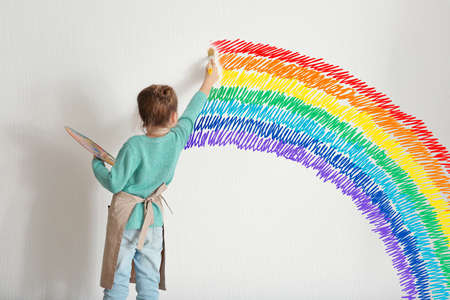 Foto de Childhood concept. Little painter drawing rainbow on white wall background - Imagen libre de derechos