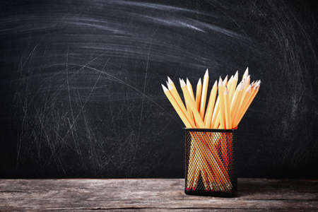Photo for Holder with pencils on wooden table against school blackboard - Royalty Free Image