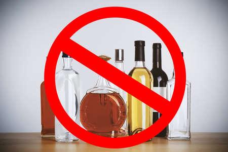 Foto de Different alcohol drinks in bottles with STOP sign on grey background - Imagen libre de derechos