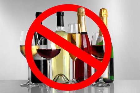 Foto de Different alcohol drinks in glassware with STOP sign on grey background - Imagen libre de derechos