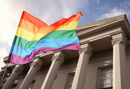 Foto de Waving gay flag and courthouse on background. LGBT right concept - Imagen libre de derechos