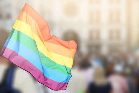 Foto de Waving gay flag and crowd of people on background. Concept of LGBT rights and parade - Imagen libre de derechos