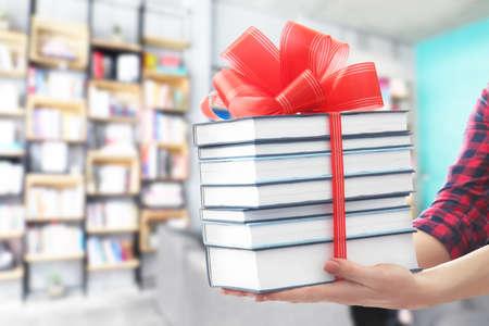 Foto de Woman holding books with ribbon bow as gift at library - Imagen libre de derechos