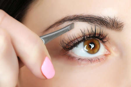 Photo pour Young woman plucking eyebrows with tweezers close up - image libre de droit