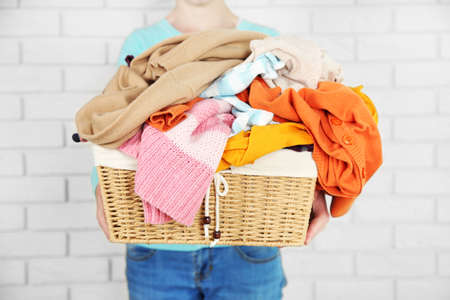 Photo pour Woman holding basket with heap of different clothes, on bricks wall background - image libre de droit