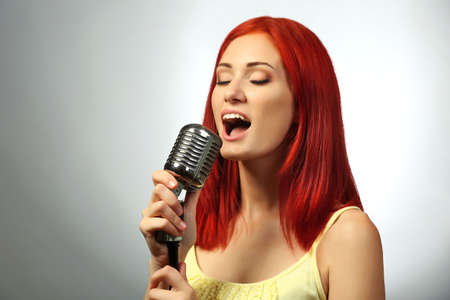 Photo for Beautiful young woman with microphone on gray background - Royalty Free Image