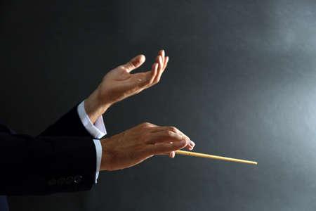 Photo pour Music conductor hands with baton on black background - image libre de droit