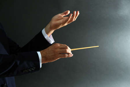 Photo for Music conductor hands with baton on black background - Royalty Free Image