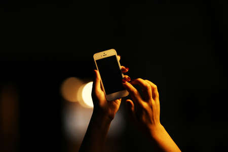 Photo pour Female hand with mobile phone on blurred night lights background - image libre de droit