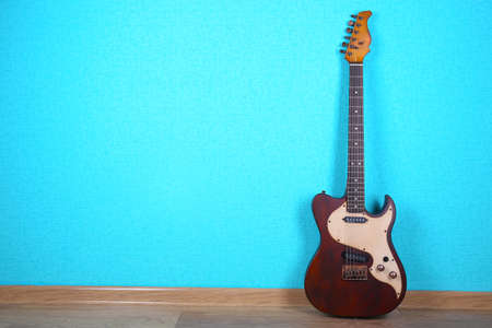 Photo for Electric guitar on blue wallpaper background - Royalty Free Image