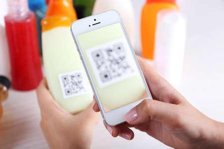 Foto de Woman scanning voucher code with mobile phone close up - Imagen libre de derechos