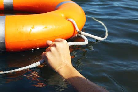 Foto de Hand holds a cord of a life buoy - Imagen libre de derechos