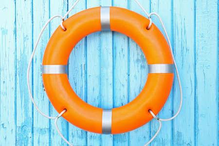 Photo pour A life buoy on blue wooden background - image libre de droit