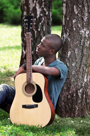 Photo for Handsome African American man with guitar sitting in park - Royalty Free Image