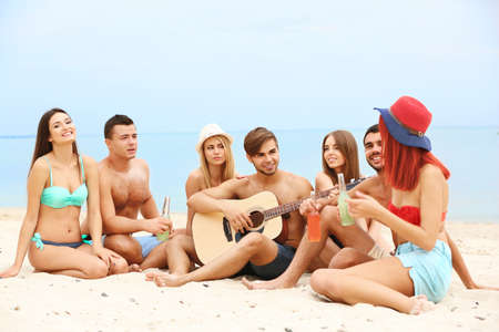 Photo for Beautiful young people with guitar having fun on beach - Royalty Free Image