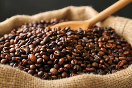 Photo pour Sac with roasted coffee beans with spoon on dark background - image libre de droit