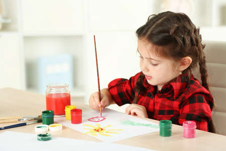 Foto de Cute little girl painting picture on home interior background - Imagen libre de derechos