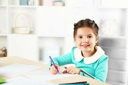 Foto de Cute little girl doing her homework, close-up, on home interior background - Imagen libre de derechos