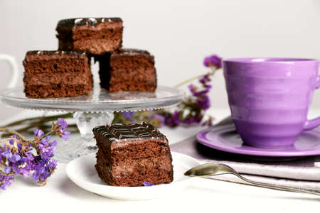 Photo for Served table with chocolate cakes and a cup of tea on white wooden background - Royalty Free Image