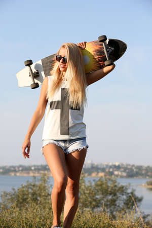 Photo pour Young woman with skating board on the riverside - image libre de droit