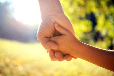 Photo pour A parent holds the hand of a small child - image libre de droit