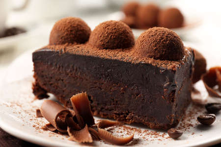 Photo for Slice of chocolate cake with a truffle on plate closeup - Royalty Free Image