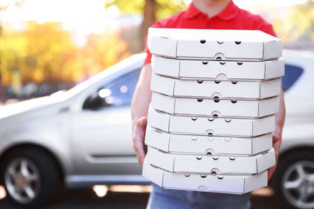 Photo pour Pizza delivery boy holding boxes with pizza near car - image libre de droit