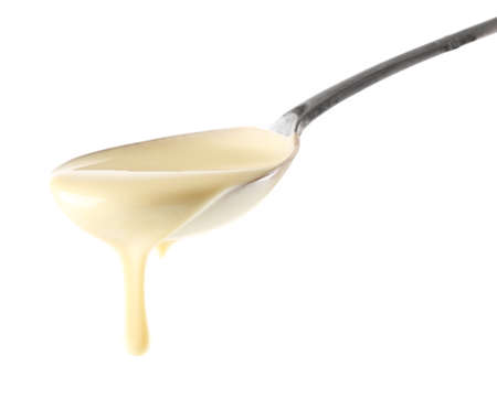 Photo for Condensed milk pouring from a spoon, isolated on white - Royalty Free Image