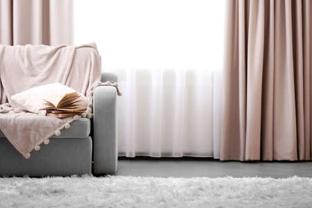 Foto de Opened book on comfortable sofa against window in the room - Imagen libre de derechos