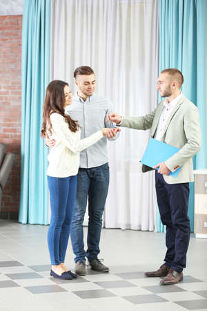 Photo for Estate agent giving keys to  couple, on light background - Royalty Free Image