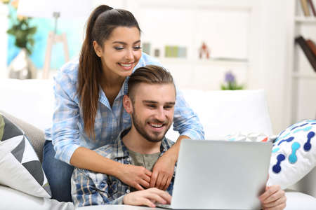 Photo for Happy couple sitting at the table and working with a laptop - Royalty Free Image