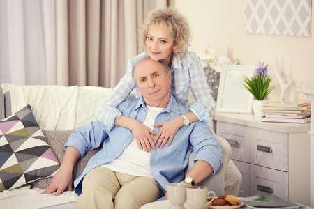 Foto de Mature couple sitting together  on a sofa at home - Imagen libre de derechos