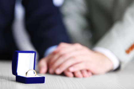 Photo pour Couple of homosexuals and wedding ring on a table - image libre de droit