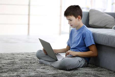 Photo pour Little boy using laptop on a floor at home - image libre de droit