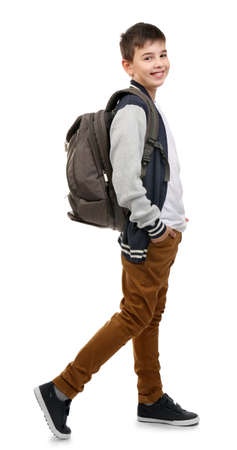 Foto de Cute little boy with grey backpack going right, isolated on white - Imagen libre de derechos