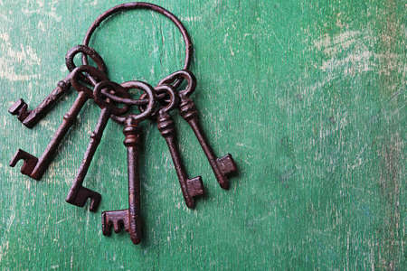 Photo for Bunch of old keys on green scratched wooden background, close up - Royalty Free Image