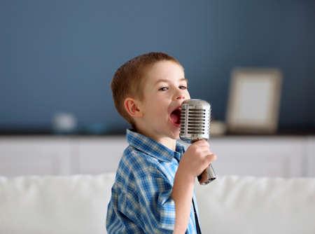 Photo pour Little boy singing into the microphone at home - image libre de droit