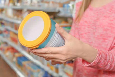 Foto de Young woman choosing baby food in supermarket, closeup - Imagen libre de derechos
