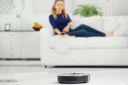 Foto de Robotic vacuum cleaner cleaning the room while woman resting on sofa - Imagen libre de derechos