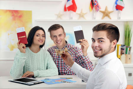 Foto de Agent and happy young couple with passports and tickets in the office of travel company - Imagen libre de derechos