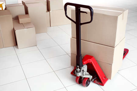 Photo pour Fork pallet truck with stack of cardboard boxes indoors - image libre de droit