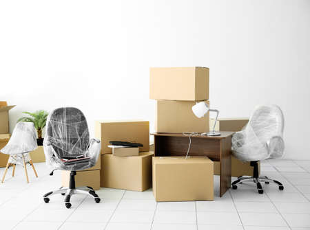 Foto de Moving cardboard boxes and personal belongings in empty office space - Imagen libre de derechos